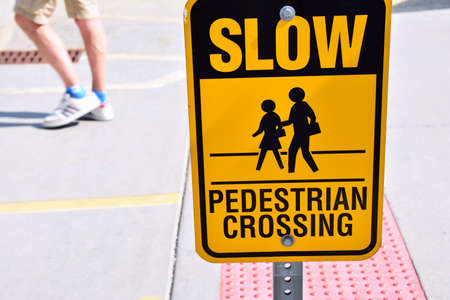 Slow pedestrian crossing yellow sign.