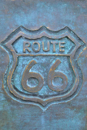 Old route 66 sign in bronze with green color. Imagens