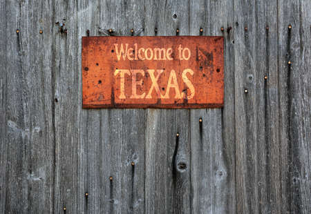 Rusty metal sign on wooden wall with the phrase: Welcome to Texas. Stock Photo