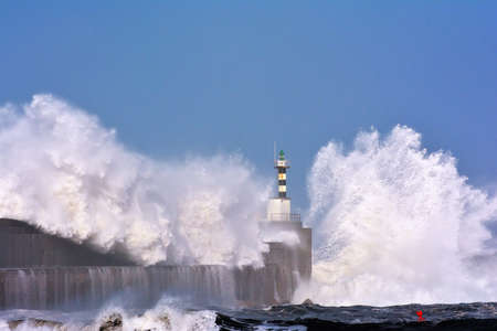 Stormy wave over lighthouse and pier of San Esteban de Pravia in Asturias, Spain. Stock Photo