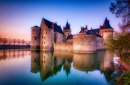 Sully Sur Loire, France - April 13, 2019: Famous medieval castle Sully sur Loire at sunset, Loire valley, France. The chateau Sully sur Loire dates from the end of the 14th century and is a prime example of medieval fortress.