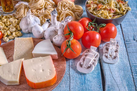 Italian cuisine with a set of ingredients for cooking pasta on a wooden surface.