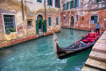 Venice, Italy - October 12, 2019: Gondolier on gondola at canal in Venice, Italy. Gondola trip is the most popular touristic activity in Venice.