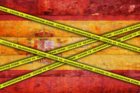 COVID-19 warning yellow ribbon written with: Quarantine zone Cover 19 on Spain flag illustration. Coronavirus danger area, quarantined country.