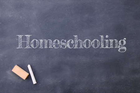 Homeschooling written on a vintage blackboard in school. Covid 19 Stockfoto