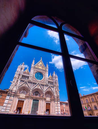 Siena, Italy - July 4, 2018: Siena Cathedral (Duomo di Siena) is a medieval church, now dedicated to the Assumption of Mary, completed between 1215 and 1263, Siena, Italy. View through a window Redactioneel