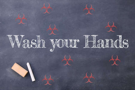 Coronavirus pandemic behaviour rules or health advice. Wash your hands chalkboard inscription.