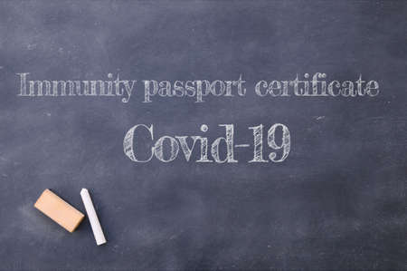 Immunity passport certificate Covid-19 written on a blackboard.