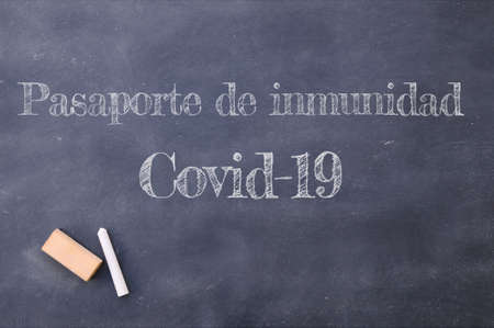 Covid-19 immunity passport written in Spanish on a blackboard.