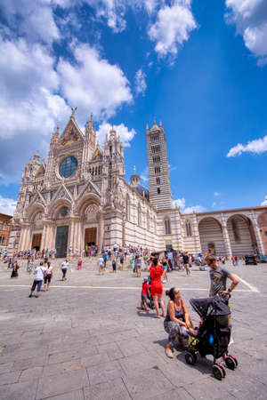 Siena, Italy - July 4, 2018: Siena Cathedral (Duomo di Siena) is a medieval church, now dedicated to the Assumption of Mary. People walking through its square