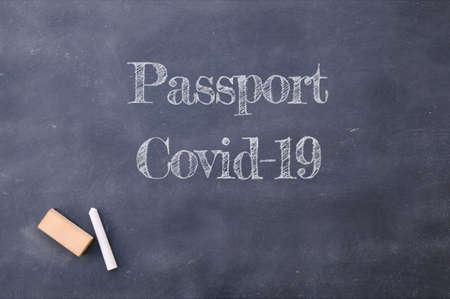 Passport Covid-19 written on a school blackboard.