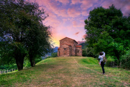 Exterior view of St Christine of Lena church at spring. Santa Cristina de Lena is a Catholic pre-Romanesque church located in Asturias, Spain. Woman photographing