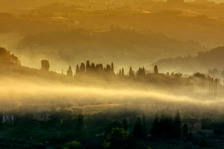 Beautiful dawn with fog at San Gimignano medieval village, Italy.
