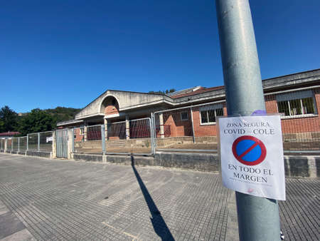 Sign written in Spanish of forbidden to park near the school, covid 19.