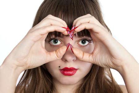 watch over: The Beautiful young woman making Hand Binoculars. Shot in studio over white.