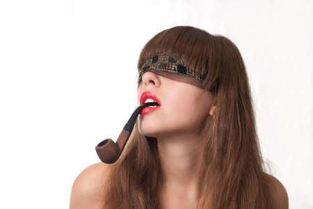 The beautiful girl blindfold and a pipe in lips photo
