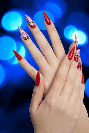 Girl fingers with beautiful drawing on nails over abstract spots of blue lights