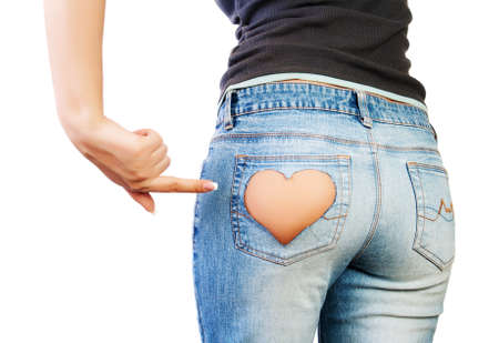 Girl in jeans with heart-shaped hole on the buttock, indicates the finger photo