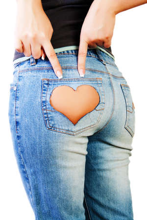 Girl in jeans with heart-shaped hole on the buttock, indicates the two fingers photo