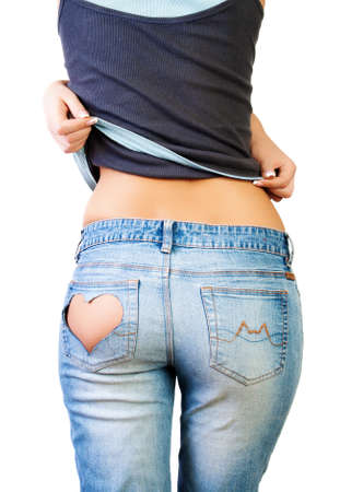 Girl in jeans with heart-shaped hole on the buttock, removes a T-shirt photo