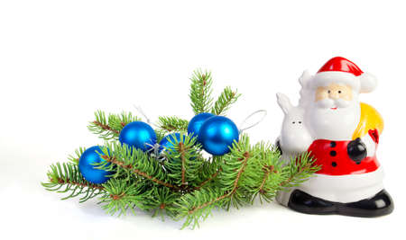 Figurine Santa Claus, christmas balls and decoration on fir tree branch