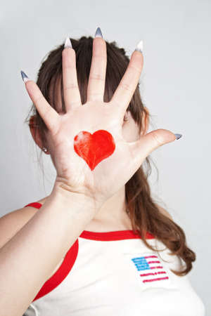 The girl closed the person at hand with the heart symbol on a gray background