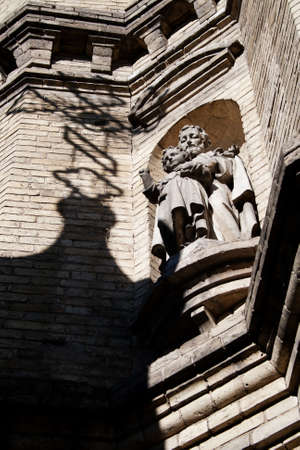 Statue sacred with the child on a facade of a building of church, with a shade from a cross