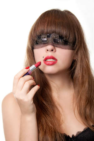 The woman blindfold hold red lipstick near lips photo