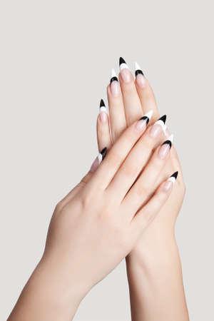 uñas largas: Dos manos con uñas hermosas en forma aguda graybackground Foto de archivo
