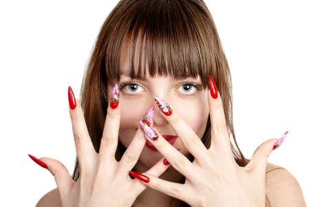 uñas largas: Joven y bella mujer con largas uñas rojas, sobre su rostro, sobre fondo blanco