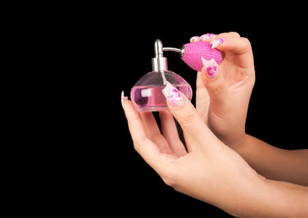 The female hand with beautiful nails holds a bottle of perfume, on a black background Stock Photo - 11700608