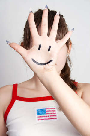 The girl closed the person at hand with the smile symbol on a gray background Stock Photo