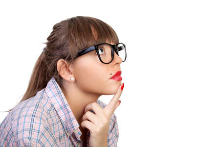 Profile of the young woman in spectacles, it is interested looking, having put a finger on a chin Stock Photo