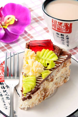 Piece of cake on a plate with fork and cup of tea on table
