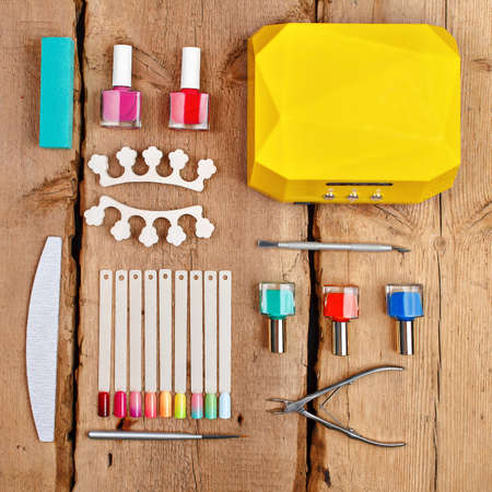 Manicure and pedicure tools on wooden background. Flat lay