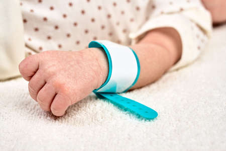 Hand eines neugeborenen Babys mit einem Namensschildarmband an seiner Hand. Konzept Mutter- oder Vatertag, erste Lebenstage im Kreißsaal.
