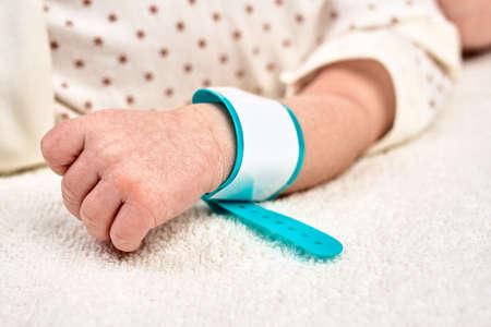 一个新出生的婴孩的手有一个名牌镯子的在他的手上。概念母亲或父亲节,在交付室的第一天生活。