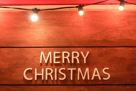 white text merry christmas on wooden background