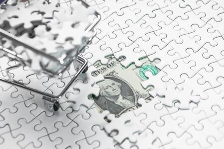 Shopping cart full of jigsaw puzzle on money dollar background, Business solution concept ,key for success Banque d'images