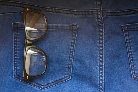 glasses in back blue jeans pocket denim background texture.