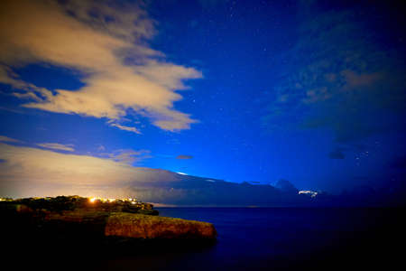 Beautiful starry sky with a thunderstorm in the sea in the background Stock Photo