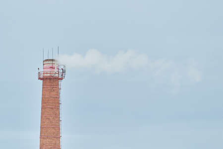 Smoking old red brick chimney with blue sky on the bachground with space to writing Stock Photo