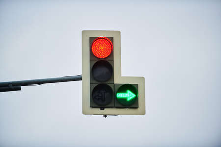 Traffic light with stop signal and green arrow on the background of cloudy sky Фото со стока