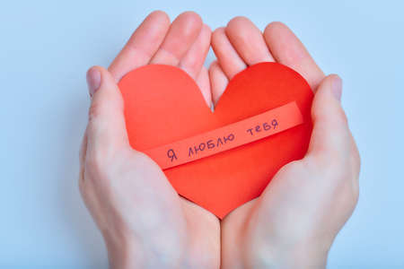 Hands with handmade red paper heart with russian words of love on the blue background