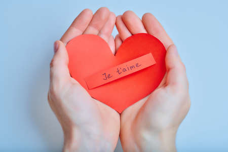 Hands with handmade red paper heart with french words of love on the blue background