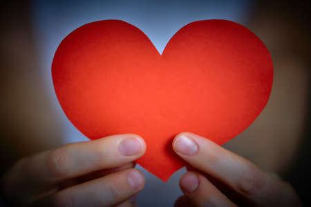 Valentines Day theme with red paper heart in young womans hands, close-up Stock Photo
