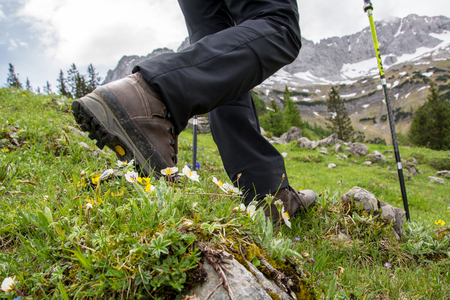 Hiking in the mountains with brown hiking boots and sticks Stock Photo