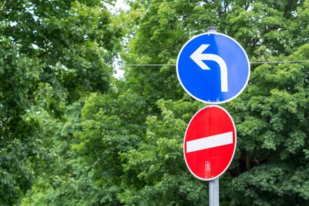 one lane road sign: Two street signs showing wrong direction and having to turn left
