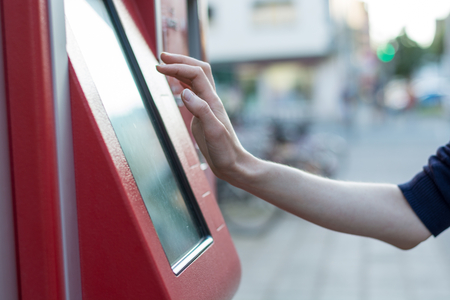 Touching on a red German ticket machine in the street