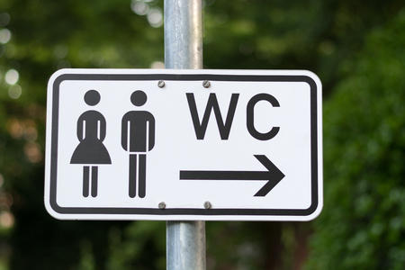 A WC sign isolated on a pole in a park
